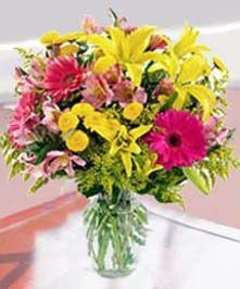 Yellow lilies, pink daisies and mixed flowers in a clear glass vase.