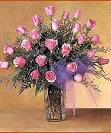 Two dozen pink roses in a clear glass vase.