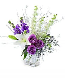 White lilies and larkspur with lavender roses and stock in a clear glass cube vase.