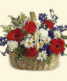 Basket filled with red, white and blue flowers for a patriotic tribute.