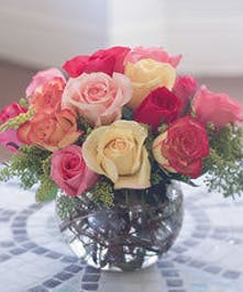 Pastel roses arranged in a bubble bowl vase.