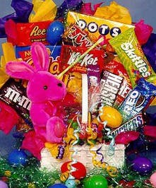 Easter basket filled with various candy and topped with a pink plush bunny.