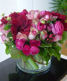 Hot pink roses, ranunculus, lilies and more in a low cylindrical vase.
