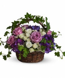 Sympathy basket of lavender, purple and white flowers with greenery.