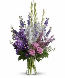 Lavender, purple and white flowers in a clear glass vase.