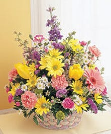 Flowers in various pastel shades in a woven basket.