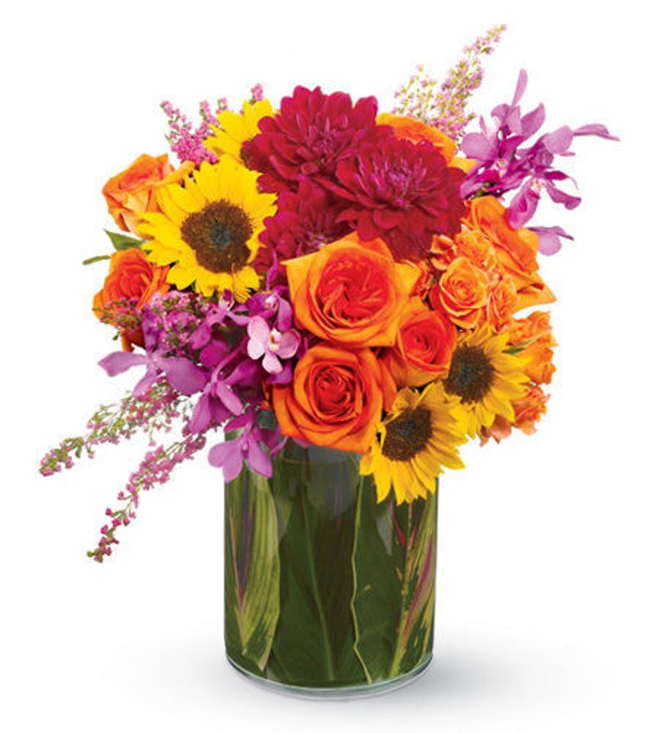 Orange, coral and purple flowers in a clear glass leaf-lined vase.
