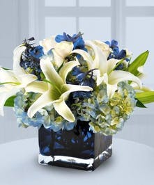 White lilies, blue hydrange and delphinium in a blue glass cube vase.