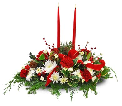 Christmas centerpiece of red and white flowers, greenery and red taper candles accented with ribbon