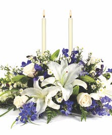 Hanukkah centerpiece with two white taper candles and blue and white flowers