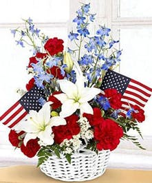 White wicker basket with red, white and blue flowers and two miniature American flags.