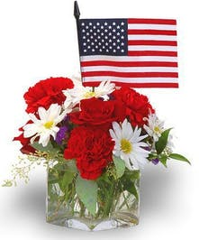 Clear glass cube vase filled with red, white and blue flowers and a miniature American flag.