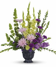 Urn of green, lavender and purple flowers accented with greenery.