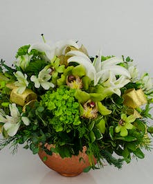 Copper bowl filled with green orchids, hydrangea, lilies and evergreen