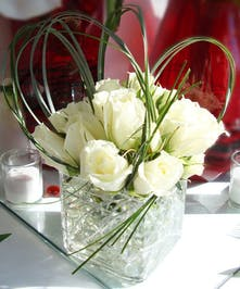 Clear cube vase filled with white roses, greenery and glass gems