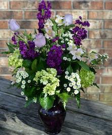 Purple stock, lavender roses, green hydrangea, asters and alstromeria in a glass vase.