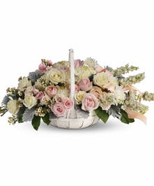 White basket of white and light pink flowers accented with satin ribbon.