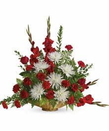 Sympathy basket of red and white flowers with assorted greenery.