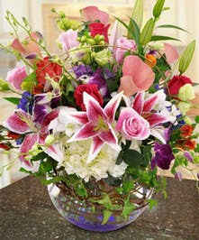 Lilies, hydrangea, roses and more in a bubble bowl vase.