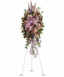 Sympathy spray of lavender, purple and pink flowers with assorted greenery and a pink organza ribbon.