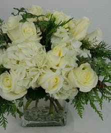 All-white arrangement accented with winter greenery in a clear glass cube