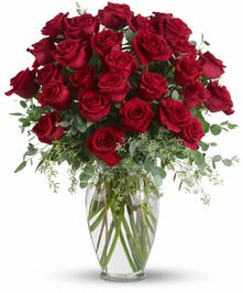 30 Red roses and eucalyptus in a clear glass vase.