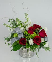 Silver vase filled with red roses and green accents with a silver bow