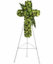 Sympathy cross of green flowers and assorted greenery presented on an easel.