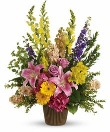 Sympathy bouquet of pink, lavender, yellow, and purple flowers with greenery.