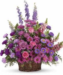 Lavender, pink and purple flowers in a round wicker basket.