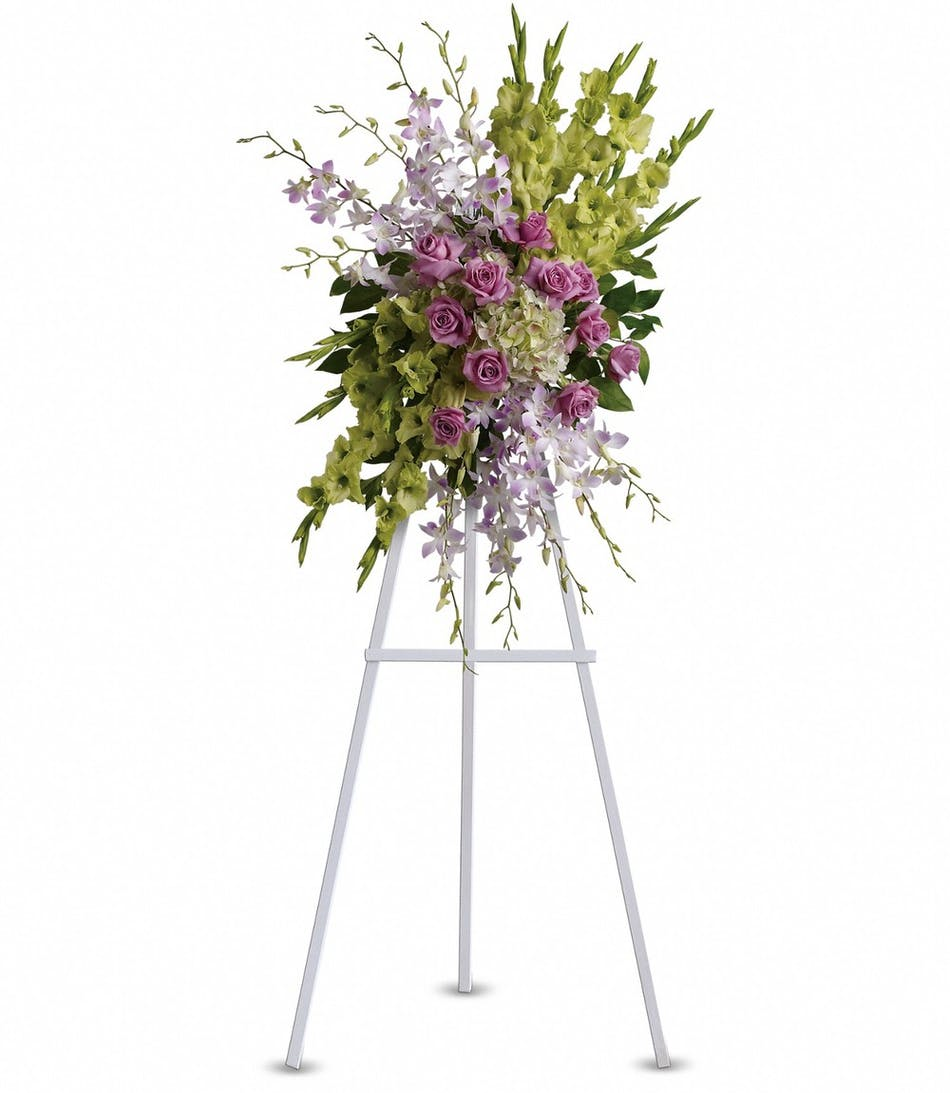 Heavenly sentiments funeral flowers by julias florist symapthy spray with flowers in shades of green purple and lavender displayed on an easel izmirmasajfo
