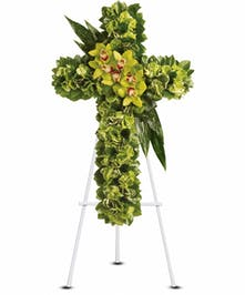 Sympathy cross of green hydrangea and exotic flowers presented on an easel.