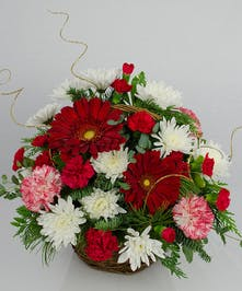 Winter basket of red, white and pink flowers with holiday greenery