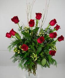 One dozen red roses with holiday greenery and hypericum berries in a designer vase