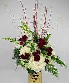 Gold geometric vase filled with seasonal red and white flowers and winter greenery