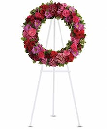 Sympathy wreath of pink, hot pink, red, burgundy and lavender flowers with greenery.