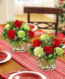 Cube centerpiece of red roses, green carnations, greenery and ornaments.