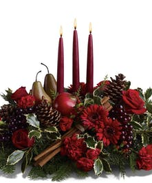 Christmas centerpiece of red flowers, faux fruit, and evergreens around three tall red taper candles.