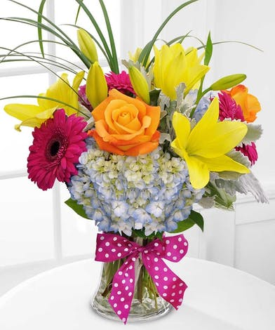 Yellow lilies, orange roses, blue hydrangea and magenta gerbera daisies in a clear glass vase.
