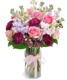 Purple, red and pink flowers in a glass vase tied with a pink ribbon.