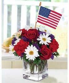 Clear glass cube of red, white and blue flowers with a miniature American flag.