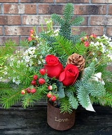 Jar filled with seasonal evergreens, berries, red roses and wax flower