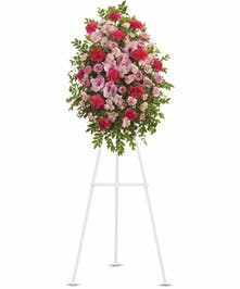 Pink, hot pink and light pink flowers displayed on an easel with greenery.