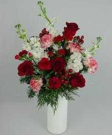 Red, white and pink flowers with winter greenery in a white cylinder vase