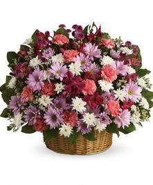 Wicker basket of pink, lavender and white flowers and assorted greenery.