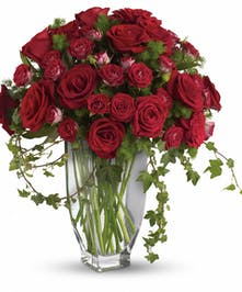 Red roses and spray roses with fern and ivy in a glass vase.