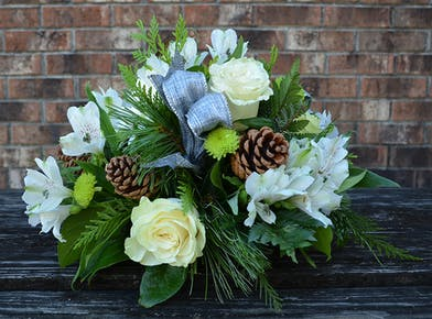 Holiday centerpiece of white flowers, greenery, pinecones and silver ribbon.