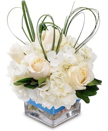 White and blue flowers with greenery in a clear glass cube vase tied with blue ribbon.
