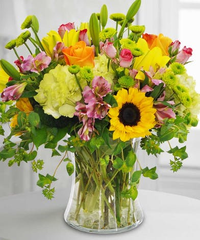Hydrangea, sunflowers and roses in a clear glass vase.