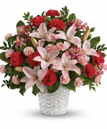 Sympathy basket of pink and hot pink flowers with assorted greenery.
